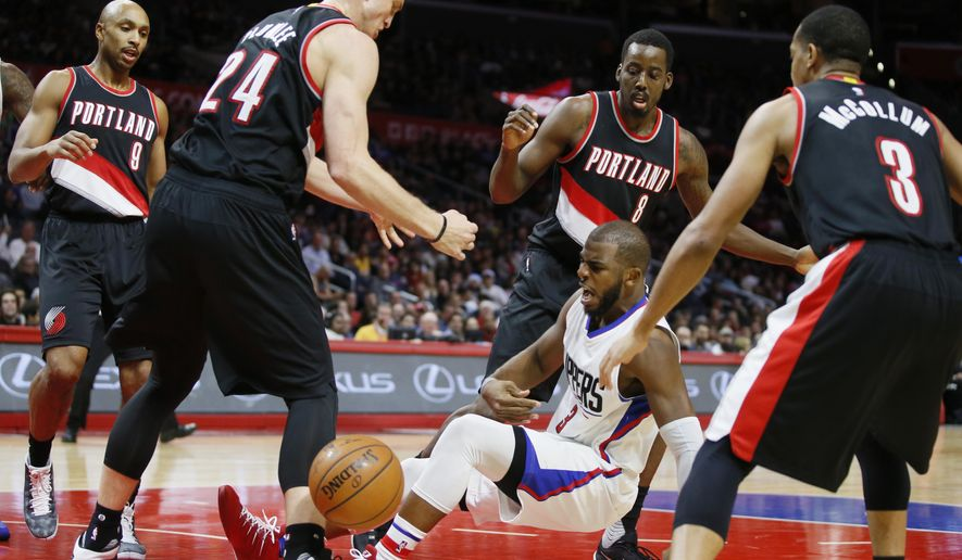 Los Angeles Clippers' Chris Paul falls while losing grasp of an offensive rebound as he is surrounded by Portland Trail Blazers', from left to right, Gerald Henderson, Mason Plumlee, Al-Farouq Aminu, and C.J. McCollum during the first half of an NBA basketball game, Monday, Nov. 30, 2015, in Los Angeles. (AP Photo/Danny Moloshok)