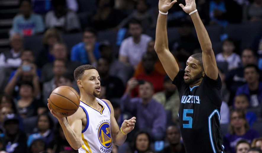 Golden State Warriors guard Stephen Curry, left, passes around Charlotte Hornets Charlotte Hornets guard Nicolas Batum, of France, in the first half of an NBA basketball game Wednesday, Dec. 2, 2015 in Charlotte, N.C. (AP Photo/Nell Redmond)