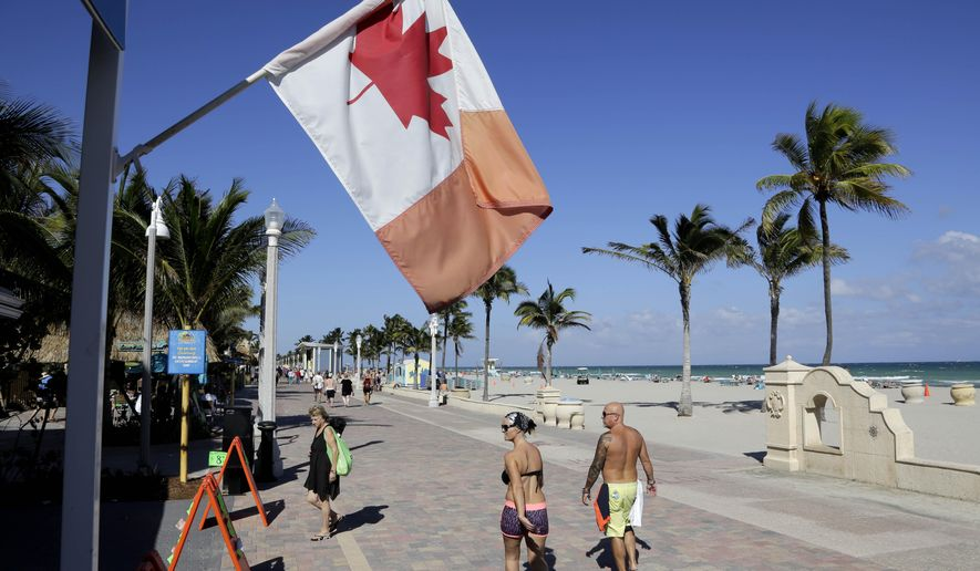In this Monday, Nov. 23, 2015 photo, a Canadian flag flies as people walk along the boardwalk in Hollywood, Fla. Visits by the United States' largest supply of international visitors from Canada are expected to be down by 8 percent this year due to the weak Canadian dollar. (AP Photo/Lynne Sladky)