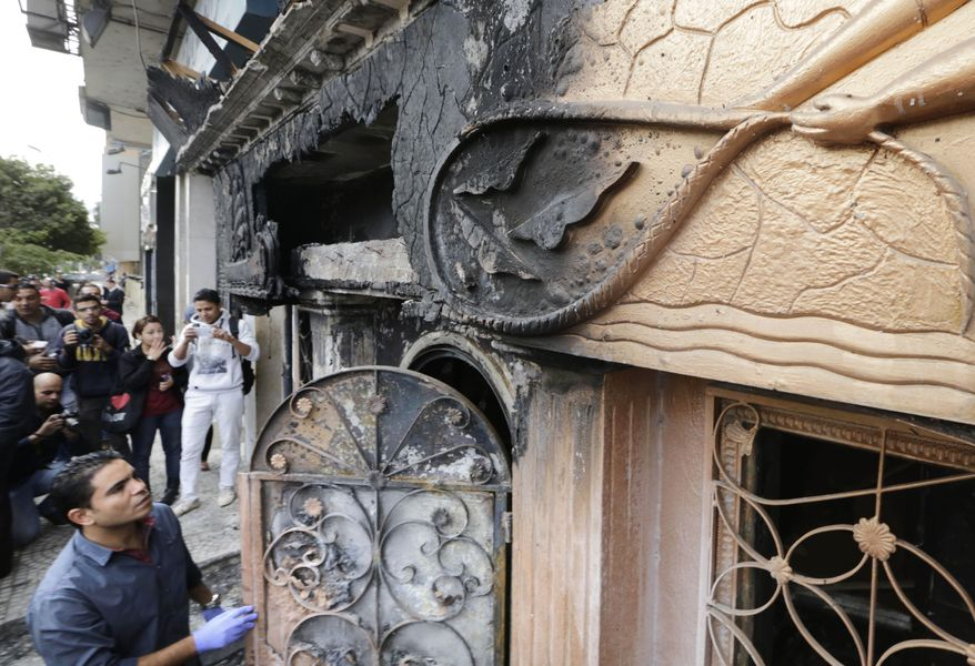 An Egyptian forensic member checks the entrance of a nightclub which was attacked in Cairo, Egypt, Friday, Dec. 4, 2015. More than a dozen were killed and wounded, Egypt's state-run news agency reported. MENA quoted an unnamed security official as saying three men on a motorcycle threw Molotov cocktails into the club in the Agouza district and then fled. (AP Photo/Amr Nabil)