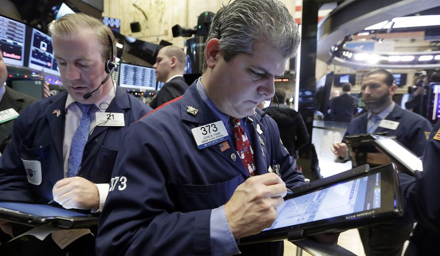Traders James Doherty (left) and John Panin (center) work on the floor of the New York Stock Exchange on Dec. 4, 2015. (Associated Press)