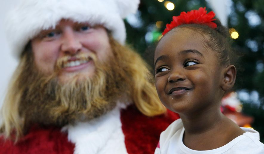 Lian Taylor, 2, right, of Bayonne, N.J., sits on the lap of New York Jets center Nick Mangold posing as Santa Claus during the team's holiday party for military families, Friday, Dec. 4, 2015, in Florham Park, N.J. The event, hosted by the Atlantic Health Jets Women's Organization, honored 18 military families. (AP Photo/Julio Cortez)