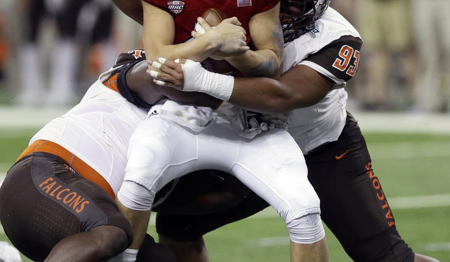 Northern Illinois quarterback Tommy Fiedler, center, is sacked by Bowling Green defensive linemen Taylor Royster, left, and Shannon Smith (93) during the first half of the Mid-American Conference championship NCAA college football game, Friday, Dec. 4, 2015, in Detroit. (AP Photo/Carlos Osorio)