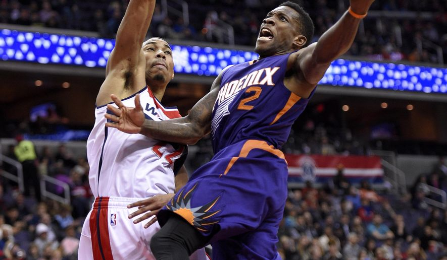 Phoenix Suns guard Eric Bledsoe (2) goes to the basket against Washington Wizards forward Otto Porter Jr. (22) during the first half of an NBA basketball game Friday, Dec. 4, 2015, in Washington. (AP Photo/Nick Wass)