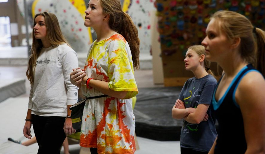 Emily Myers, from left, Jane Cottrell, Natalie Bushman and Hazel Christiansen, members of the High School Climbing League, watch as coach Mercedes Cademartori demonstrates climbing technique at Momentum Indoor Climbing in Lehi, Utah, Monday, Nov. 16, 2015. High school students from different schools share a gym and climb together, and there are no rivalries among them. They would find camaraderie and support among their fellow teammates and competitors. (Spenser Heaps/The Daily Herald via AP) MANDATORY CREDIT
