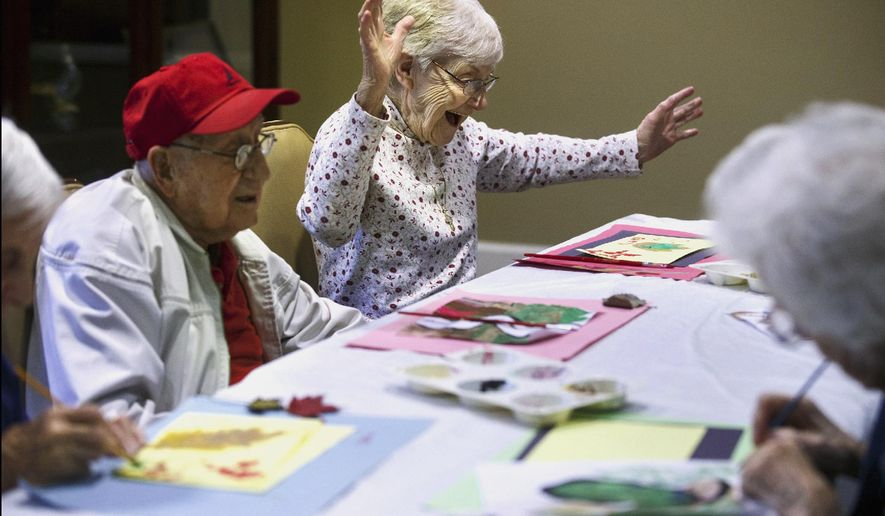 In this Nov. 16, 2015 photo, Betty Green reacts to a painting she was working on at Mill Creek Alzheimer's Special Care Center in Springfield, Ill. A new $2.8 million center, under construction in Riverton and scheduled to open in March 2016, will be one of a growing number of residential options for people with memory-related disorders in the Springfield area. (Ted Schurter/The State Journal-Register via AP) MANDATORY CREDIT, NO SALES