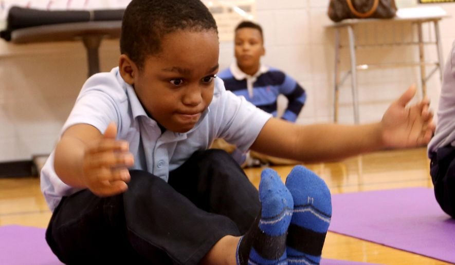 Davon Ethridge, 8, a third grader at the Charles Wright Academy of Arts and Sciences in Detroit, tries to reach for his toes on Nov. 17, 2015, during a yoga class at the school gymnasium in its 10th year in partnership with Detroit Public Schools, and Danialle Karmanos' Work It Out. (Jessica J. Trevino/Detroit Free Press via AP) **FILE**