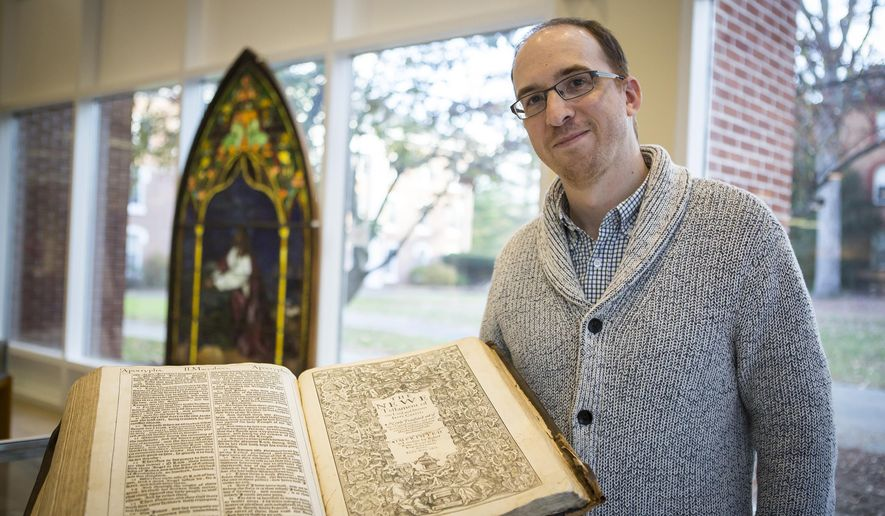 In a Friday, Nov. 13, 2015 photo, Brian Shetler, a graduate student at Drew University, poses with a first edition of the King James Bible he discovered on campus in Madison, N.J. The 1611 Bible was discovered in late October in the school's United Methodist Archives. (Lynne DeLade/Drew University via AP)
