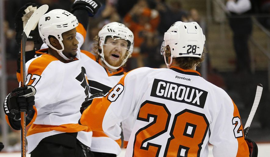 Philadelphia Flyers right wing Wayne Simmonds, left, celebrates with teammates Jakub Voracek, center, of the Czech Republic, and Claude Giroux after scoring a goal against the New Jersey Devils during the first period of an NHL hockey game Friday, Dec. 4, 2015, in Newark, N.J. (AP Photo/Julio Cortez)
