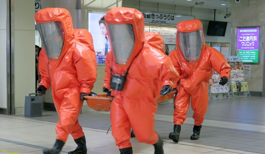 "In this Thursday, Dec. 3, 2015 photo, police officers of Aichi Prefecutral Police in full-body chemical suits carry  an ""injured person"" during an anti-terror drill at JR Owari Ichinomiya railway station in Ichinomiya, Aichi Prefecture, central Japan. Japan is preparing to launch an anti-terrorism intelligence unit next week as the country gears up for the 2020 Tokyo Olympics. The special unit will be set up within the Foreign Ministry, Chief Cabinet Secretary Yoshihide Suga said Friday, Dec. 4, 2015. (Aiko Okayama/Kyodo News via AP) JAPAN OUT, CREDIT MANDATORY"