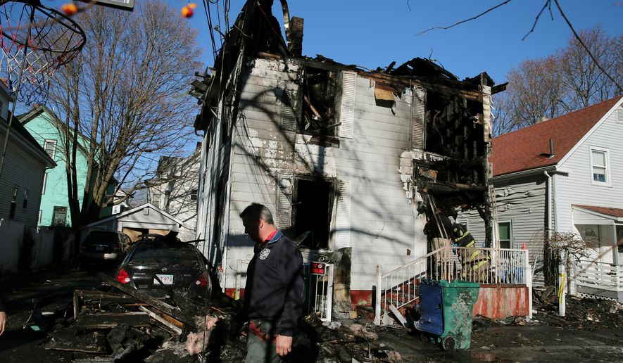 Firefighters continue to work at the scene of a fatal house fire in Lynn, Mass., on Friday, Dec. 4, 2015. Several people were killed early Friday when a powerful fire consumed the three-family home, forcing Lynn firefighters to abandon rescue efforts after entering the burning residence twice to rescue two women, according to fire and law enforcement officials. (Craig F. Walker /The Boston Globe via AP)  BOSTON HERALD OUT, QUINCY OUT; NO SALES; MANDATORY CREDIT