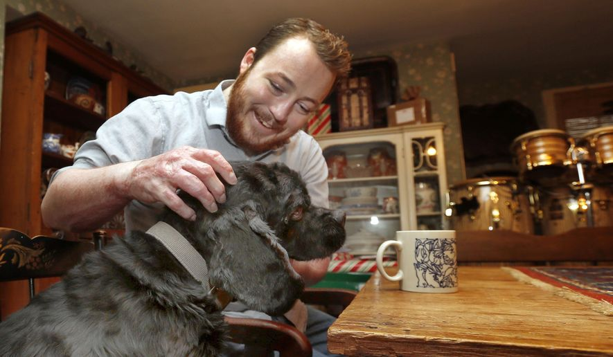 In this photo taken Wednesday Dec. 2, 2015 Alex Haas plays with his dog Charlie at his home in Mont Vernon, N.H. This past summer Haas received burns over 90 percent of his body at a Taiwan water park. (AP Photo/Jim Cole)