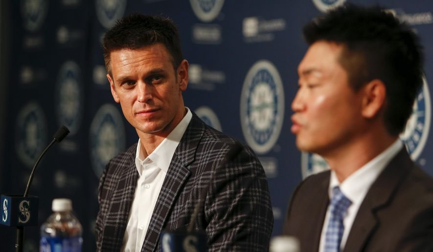 Seattle Mariners general manager Jerry Dipoto, left, listens as the team's new outfielder,Nori Aoki, answers a question during a news conference Thursday, Dec. 3, 2015, in Seattle. (AP Photo/Joe Nicholson)