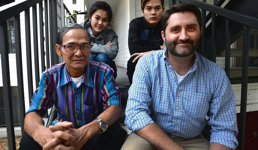 Aster Paw, 19, top left, and Nay Ree, 21, with their father Pah De Paw, left, and Alan Gardner, a volunteer for the Refugee Family Friend Program who mentors the refugee family from Myanmar, pose for a photo in Salt Lake City on Tuesday, Nov. 24, 2015. The refugee program matches volunteers with refugee families to form friendships and help the newcomers gain access to resources. (Steve Griffin/The Salt Lake Tribune via AP) MANDATORY CREDIT