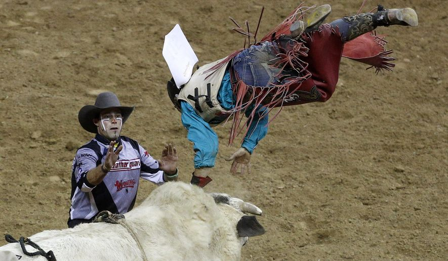 Dustin Bowen is thrown during the first go-round of bull riding at the National Finals Rodeo on Thursday, Dec. 3, 2015, in Las Vegas. (AP Photo/John Locher)