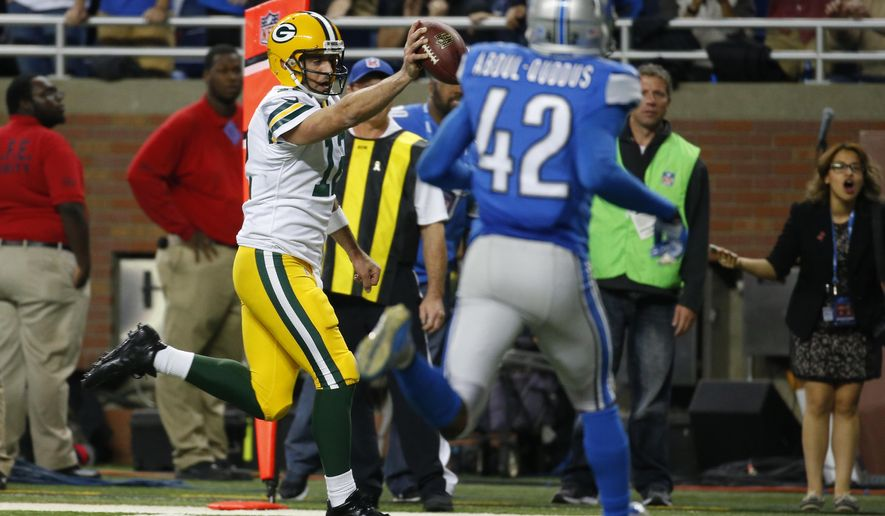Green Bay Packers quarterback Aaron Rodgers (12) scrambles into the end zone untouched for a touchdown during the second half of an NFL football game against the Detroit Lions, Thursday, Dec. 3, 2015, in Detroit. (AP Photo/Paul Sancya)