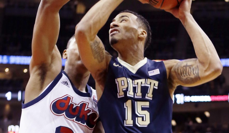 Pittsburgh's Sterling Smith (15) goes up to shoot as Duquesne's L.G. Gill (33) defends in the first half of an NCAA college basketball game, Friday, Dec. 4, 2015, in Pittsburgh. (AP Photo/Keith Srakocic)