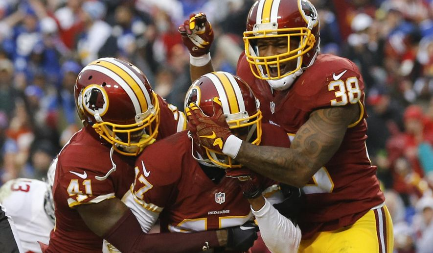 FILE - In this Nov. 29,2015 file photo, Washington Redskins cornerback Quinton Dunbar, center, is mobbed by his teammates cornerback Will Blackmon (41) and free safety Dashon Goldson (38) after he intercepted a pass in the end zone during the second half of an NFL football game against the New York Giants in Landover, Md.  At the outset of training camp for the Washington Redskins, DeAngelo Hall was a cornerback, just as he had been throughout his NFL career. And now? He's a starting safety. Back when the first practices of the preseason were unfolding, Quinton Dunbar was a rookie wide receiver. These days, he's a cornerback who's playing key minutes. (AP Photo/Patrick Semansky, File)