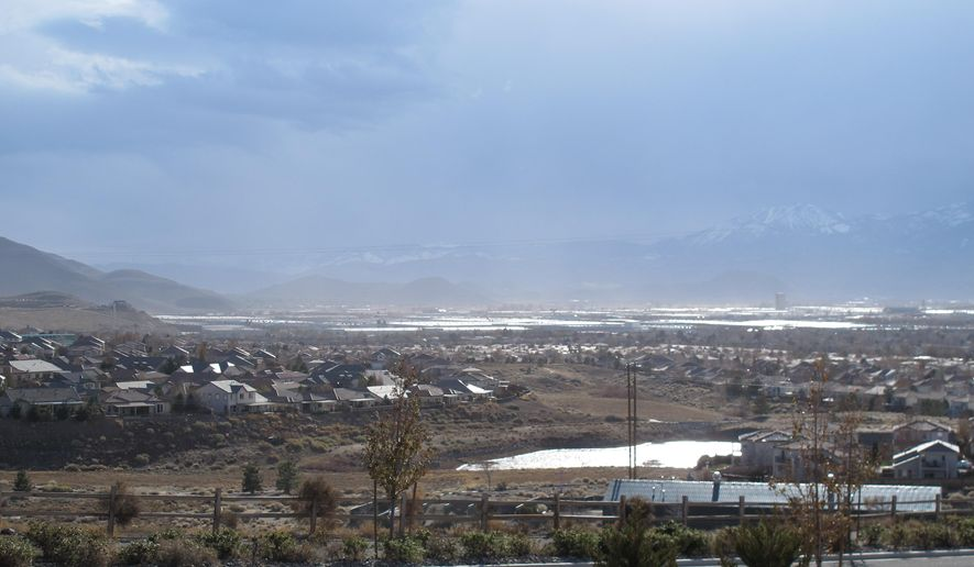 A dust storm spreads over Reno, Nev., Thursday, Dec. 3, 2015. A Sierra storm packing winds gusting to nearly 100 mph over the ridge tops blew into western Nevada on Thursday, toppling power lines, snarling traffic at dark stoplights and stirring up dusty, air quality alerts in Reno and Sparks. (AP Photo/Scott Sonner)
