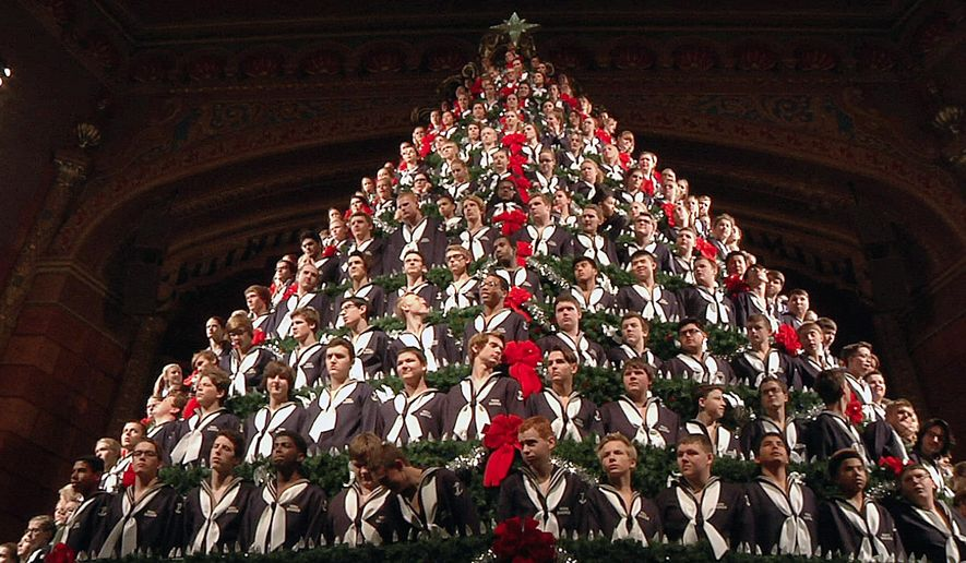 In this Wednesday, Dec. 2, 2015 photo, members of the Mona Shores High School Choir stand in the Singing Christmas Tree during a dress rehearsal performance at the Frauenthal Center in Muskegon, Mich. The five-story Singing Christmas Tree features 15 tiers on which about 220 student singers stand. (AP Photo/Mike Householder)