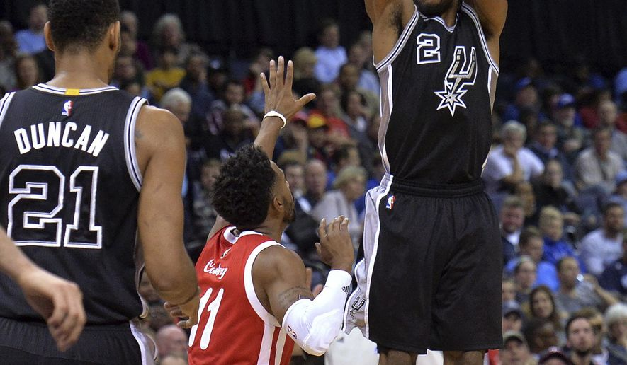 San Antonio Spurs forward Kawhi Leonard (2) shoots a 3-pointer against Memphis Grizzlies guard Mike Conley (11) during the second half of an NBA basketball game Thursday, Dec. 3, 2015, in Memphis, Tenn. (AP Photo/Brandon Dill)