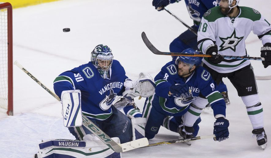 A shot deflects off the shoulder of Vancouver Canucks goalie Ryan Miller, left, as Chris Tanev (8) defends Dallas Stars' Patrick Eaves, right, during the second period of an NHL hockey game Thursday, Dec. 3, 2015, in Vancouver, British Columbia. (Darryl Dyck/The Canadian Press via AP)