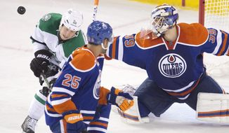 Dallas Stars' Cody Eakin (20) tries to screen Edmonton Oilers goalie Anders Nilsson (39) as Darnell Nurse (25) defends during the second period of an NHL hockey game in Edmonton, Alberta, Friday, Dec. 4, 2015. (Jason Franson/The Canadian Press via AP) MANDATORY CREDIT