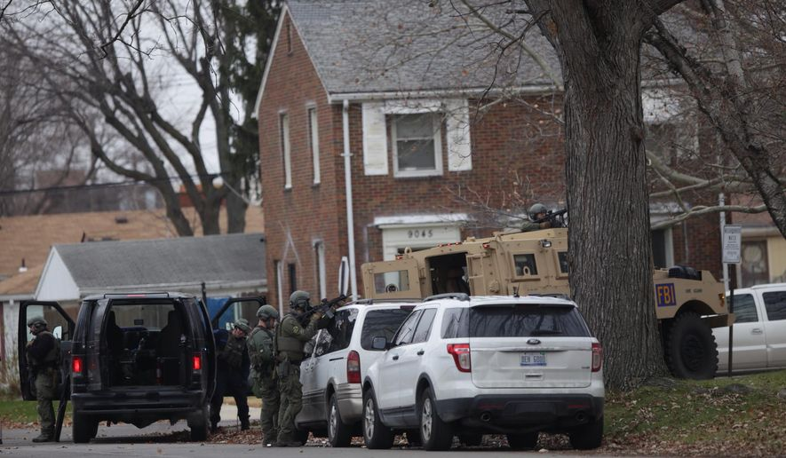 Law enforcement officers stand guard outside of a house where a suspected murderer has barricaded himself on Detroit's westside on Friday, Dec. 4, 2015. (Romain Blanquart/Detroit Free Press via AP)