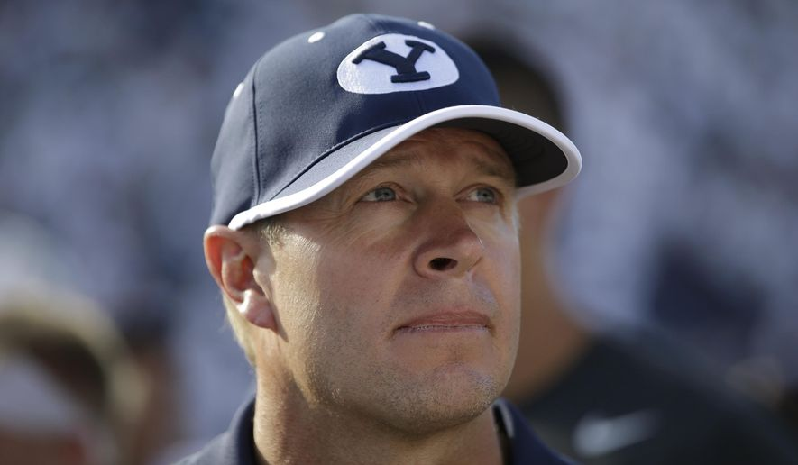 FILE - In this Sept. 20, 2014, file photo, BYU coach Bronco Mendenhall stands on the field after the team's 41-33 victory over Virginia in an NCAA college football game in Provo, Utah. Virginia has hired Mendenhall away from BYU to be the Cavaliers' new coach. (AP Photo/Rick Bowmer, File)