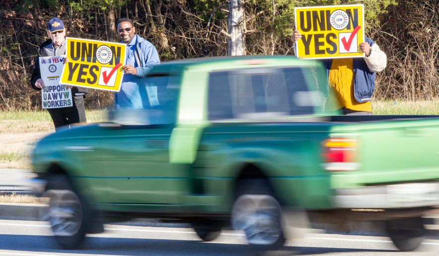 Union supporters hold up signs near the Volkswagen plant in Chattanooga, Tenn., on Friday, Dec. 4, 2015. Skilled-trades workers at the plant were voting on whether to be represented by the United Auto Workers for collective bargaining purposes. (AP Photo/Erik Schelzig)