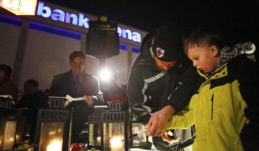 Kasey Ladd and his son, Patrick, 7, light a candle for their mother and grandmother, Teva Rae Ladd, who was 27 when she died at a concert by The Who 36 years ago, while attending a memorial marker in Cincinnati on Thursday, Dec. 3, 2015. Families of people killed in the crowd rush at the 1979 concert by The Who joined the city's mayor to dedicate the memorial marker to the victims. (Meg Vogel/The Cincinnati Enquirer via AP) MANDATORY CREDIT; NO SALES