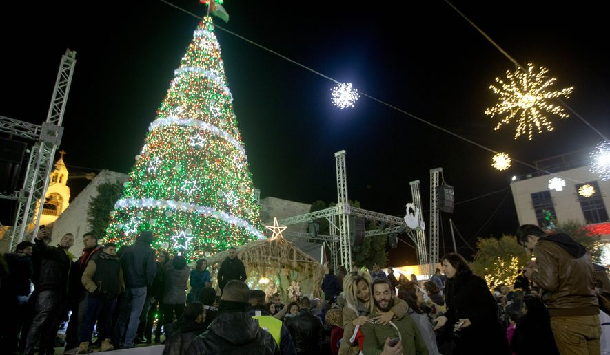 christian palestinians attend the lighting of a christmas tree in manger square outside the church