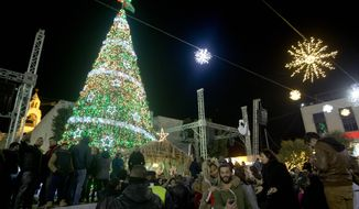 Christian Palestinians attend the lighting of a Christmas tree in Manger Square, outside the Church of the Nativity in the West Bank town of Bethlehem, Saturday, Dec. 5, 2015. Christmas Eve is a major event for the biblical town, but Mayor Vera Baboun said the city would only decorate Manger Square this year. The holiday spirit will be harder to find after weeks of Israeli-Palestinian violence. (AP Photo/Majdi Mohammed)