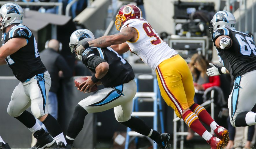 Carolina Panthers quarterback Cam Newton (1) works to avoid being tackled by Washington Redskins defensive end Jason Hatcher (97) during an NFL game at Bank of America Stadium in Charlotte, N.C. on Sunday, Nov. 22, 2015. (Chris Keane/AP Images for Panini)