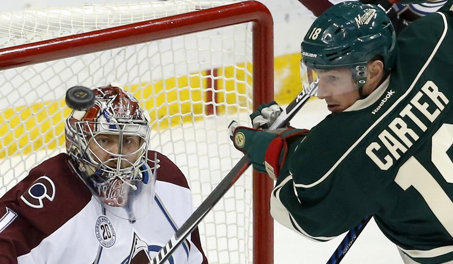 Colorado Avalanche goalie Semyon Varlamov (1), of Russia, watches the puck as Minnesota Wild center Ryan Carter (18) chases it during the first period of an NHL hockey game in St. Paul, Minn., Saturday, Dec. 5, 2015. (AP Photo/Ann Heisenfelt)