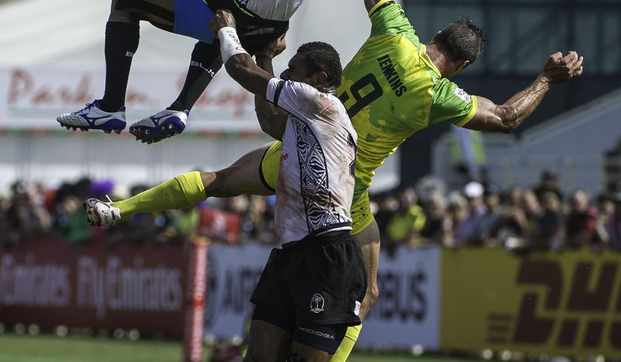 Jerry Tuwai of Fiji, top, is lifted by Jasa Veremalua as Ed Jenkins of Australia, center right, contests in the Quarter Final during the second day of the Sevens World Series rugby tournament in Dubai, United Arab Emirates, Saturday, Dec. 5, 2015.  (AP Photo/Stephen Hindley)