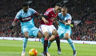 Manchester United's Anthony Martial, centre, fights for the ball against West Ham United's Alexandre Song, left, and Winston Reid during the English Premier League soccer match between Manchester United and West Ham United at Old Trafford Stadium, Manchester, England, Saturday, Dec. 5, 2015. (AP Photo/Jon Super)