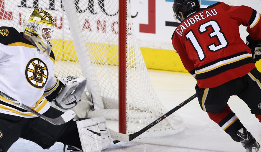 Calgary Flames' Johnny Gaudreau, left, scores on Boston Bruins goalie Jonas Gustavsson, from Sweden, during the second period of an NHL hockey game Friday, Dec. 4, 2015, in Calgary, Alberta. (Larry MacDougal/The Canadian Press via AP)