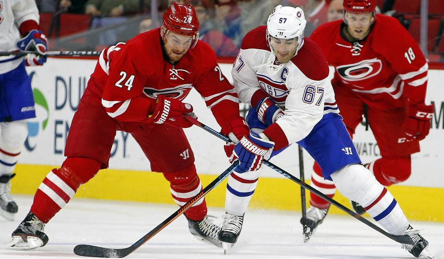 Carolina Hurricanes' Brad Malone (24) competes with Montreal Canadiens' Max Pacioretty (67) for the puck during the first period of an NHL hockey game, Saturday, Dec. 5, 2015, in Raleigh, N.C. (AP Photo/Karl B DeBlaker)