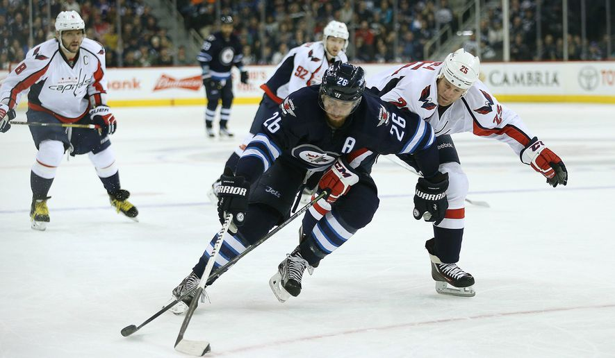 Winnipeg Jets' Blake Wheeler (26) attempts to get around Washington Capitals' Jason Chimera (25) as he drives for the net during the second period of an NHL hockey game in Winnipeg, Manitoba on Saturday, Dec. 5, 2015. (John Woods/The Canadian Press via AP) MANDATORY CREDIT