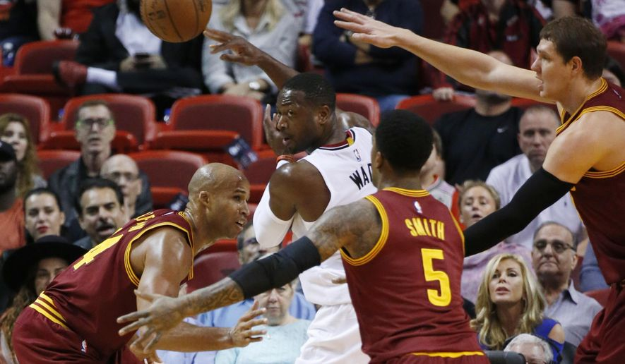 Miami Heat guard Dwyane Wade, center rear, passes around Cleveland Cavaliers forward Richard Jefferson, left, guard J.R. Smith, center, and center Timofey Mozgov, right, during the first half of an NBA basketball game, Saturday, Dec. 5, 2015, in Miami. (AP Photo/Wilfredo Lee)