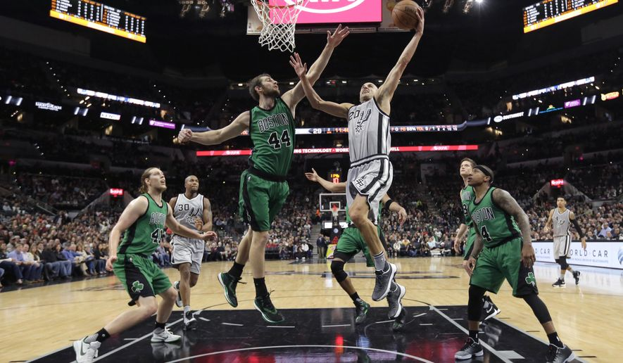 San Antonio Spurs guard Manu Ginobili (20) drives to the basket against Boston Celtics center Tyler Zeller (44) during the first half of an NBA basketball game, Saturday, Dec. 5, 2015, in San Antonio. (AP Photo/Eric Gay)