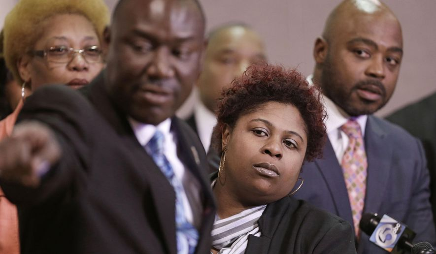 FILE- In this March 3, 2015, file photo, Samaria Rice, center, the mother of Tamir Rice, a 12-year-old boy fatally shot by a Cleveland police officer, watches the video of Tamir's shooting during a news-conference in Cleveland. Attorney Benjamin Crump, left, and attorneys Walter Madison, right, watch. Attorneys for the family of Tamir Rice have asked a prosecutor to allow their use-of-force experts to testify before the grand jury. (AP Photo/Tony Dejak, File)