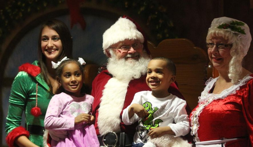 Two kids sit on Santa's lap on Dec. 1, 2015 at Division Headquarters at Fort Campbell as the post held its annual tree-lighting ceremony. (Ray Howze/The Leaf-Chronicle via AP)