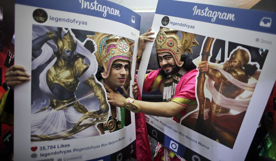 Fans dressed as Hindu mythological characters pose for photographs at Delhi Comic Con in New Delhi, India, Saturday, Dec. 5, 2015. Indian mythological heroes, dressed in gaudy costumes with bejeweled crowns and sparkly clothes, added to the carnival atmosphere of India's annual comic book fest Saturday, ready to oblige fans with an autograph, a selfie or a photograph. (AP Photo/Altaf Qadri)