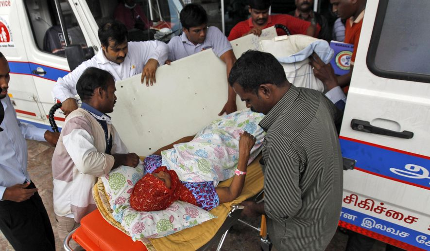 In this Friday, Dec. 4, 2015 photo, a patient is shifted to an ambulance after the hospital she was being treated in had to be shut down because of power failure and being inundated with floodwaters in Chennai, in the southern Indian state of Tamil Nadu. Officials say 18 patients who were in the intensive care unit of this hospital died when a power outage affected ventilators in the hospital, after rain waters knocked out generators of the building.  (AP Photo/Arun Sankar K)