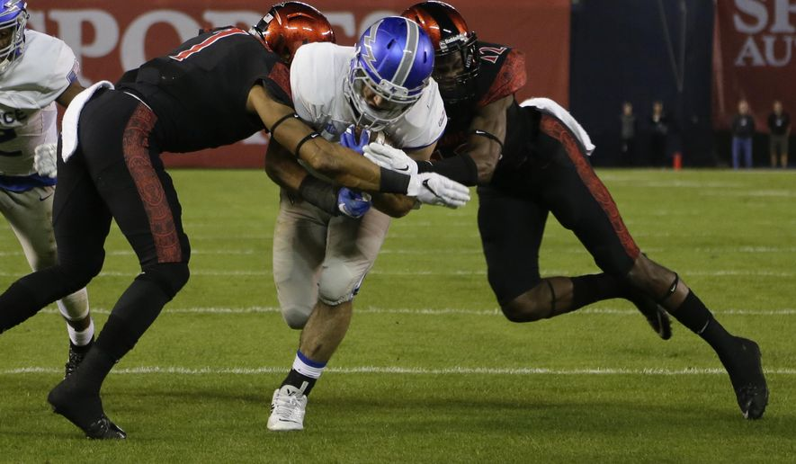 Air Force running back Timothy McVey, center, is hit by San Diego State defensive back JJ Whittaker, left, and defensive back Malik Smith, right, as he scores a touchdown during the first half of the NCAA Mountain West Championship football game Saturday, Dec. 5, 2015, in San Diego. (AP Photo/Gregory Bull)