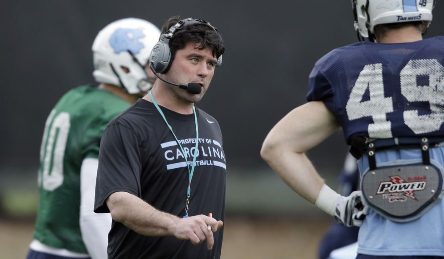 FILE - In this April 9, 2014 file photo, North Carolina's new assistant head coach for offense and tight ends Seth Littrell speaks with tight end Eric Albright (49) during an NCAA college football spring practice in Chapel Hill, N.C. A person with direct knowledge of the decision tells The Associated Press that North Texas has agreed to make Littrell its new head coach. A deal was still being finalized and the school did not plan to make an announcement until after the Tar Heels played Clemson in the Atlantic Coast Conference championship game Saturday night, Dec. 5, 2015.  (AP Photo/Gerry Broome, File)