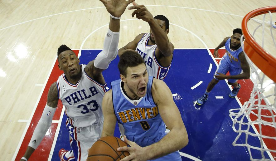 Denver Nuggets' Danilo Gallinari, center, goes up for a shot against Philadelphia 76ers' Robert Covington, left, and Hollis Thompson during the second half of an NBA basketball game, Saturday, Dec. 5, 2015, in Philadelphia. Denver won 108-15. (AP Photo/Matt Slocum)