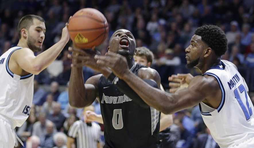 Providence forward Ben Bentil (0) looks to go up for a shot against Rhode Island guard Jarvis Garrett (1) and forward Hassan Martin (12) during the first half of an NCAA college basketball game Saturday, Dec. 5, 2015, at the Ryan Center in Kingston, R.I. (AP Photo/Stephan Savoia)